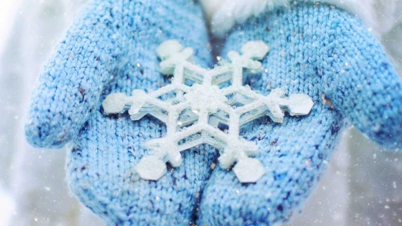Large snowflake being held on the palms of two woollen mittens with snow falling all around