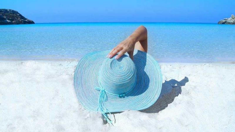 Hot, sunny day with a woman laying on a beach in a big, blue sun hat