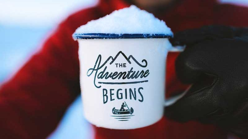 White tin mug with blue rim filled with snow and showing the logo 'The Adventure Begins'