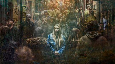 Girl feeling alone as she stands in a crowd of people