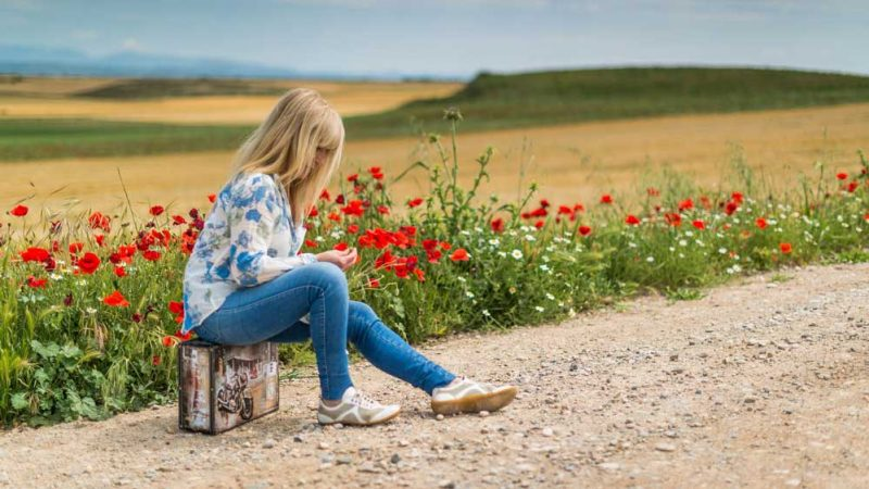 Woman sitting on a suitcase by a poppy field, passing time