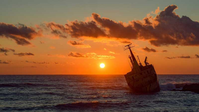 Shipwreck off the coast at sunset